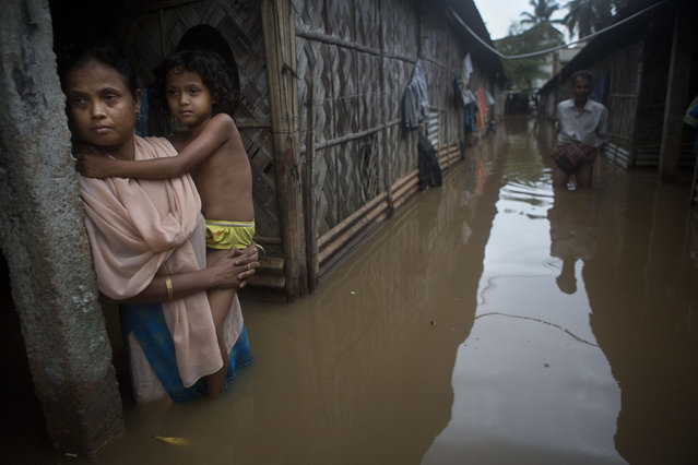 A woman holds her daughter stands awaiting her husband who went to collect drinking water after flood waters enter their house following heavy monsoon rains in Gauhati, India, Wednesday, September 23, 2015. (Photo by Anupam Nath/AP Photo)