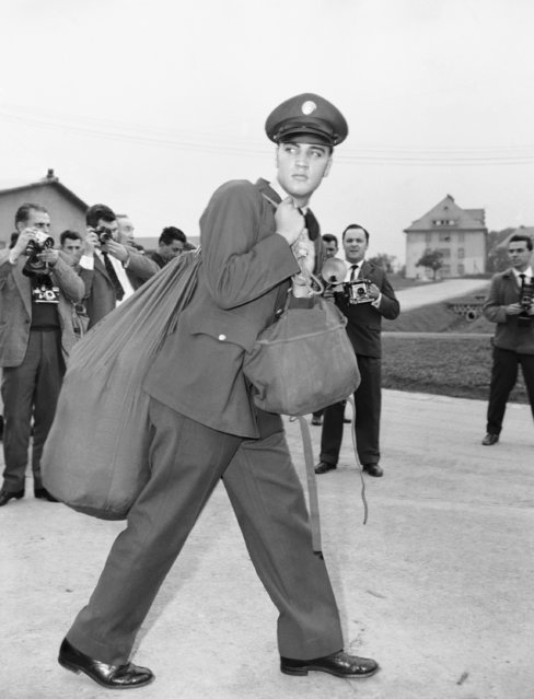 Elvis Presley carries his duffle bag as he checks in at the Friedberg, West Germany barracks on October 2,1958. He was assigned to the 3rd Armored (Spearhead) division. About 1,000 Elvis fans from Germany and other countries came to the central German spa town of Bad Nauheim to attend a day-long Elvis homage Saturday, August 26, 1995. (Photo by AP Photo)