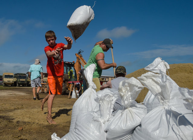 Dylan Heinan, among other volunteers, piles sandbags in an effort to stop flood waters from rising in Lake Arthur, La., Wednesday, August 17, 2016. (Photo by Scott Clause/The Daily Advertiser via AP Photo)