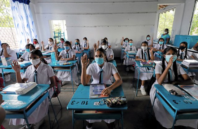Students wearing protective face masks practice keeping a one meter distance as they attend a maths lesson inside a class room on the first day at Vidyakara college, which re-opened after almost two months of lock-down amidst concerns about the spread of coronavirus disease (COVID-19), in Colombo, Sri Lanka on July 6, 2020. (Photo by Dinuka Liyanawatte/Reuters)