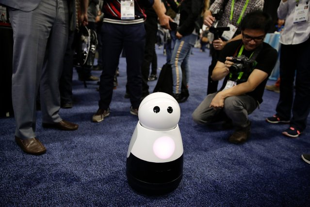 Mayfield Robotics' Kuri home robot is surrounded by attendees during CES Unveiled at CES International Sunday, January 7, 2018, in Las Vegas. (Photo by Jae C. Hong/AP Photo)