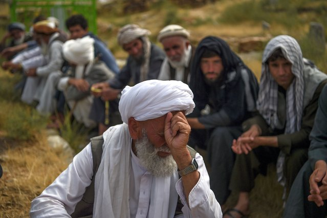 A mourner reacts as he attends a burial ceremony of the victims who died in the flash flood that affected the area, at a cemetery near Sayrah-e-Hopiyan in Charikar, Parwan province, on August 27, 2020. Rescue workers were searching on August 27 for bodies in the debris of collapsed houses after flash floods fuelled by torrential rains killed at least 162 people in Afghanistan. (Photo by Wakil Kohsar/AFP Photo)