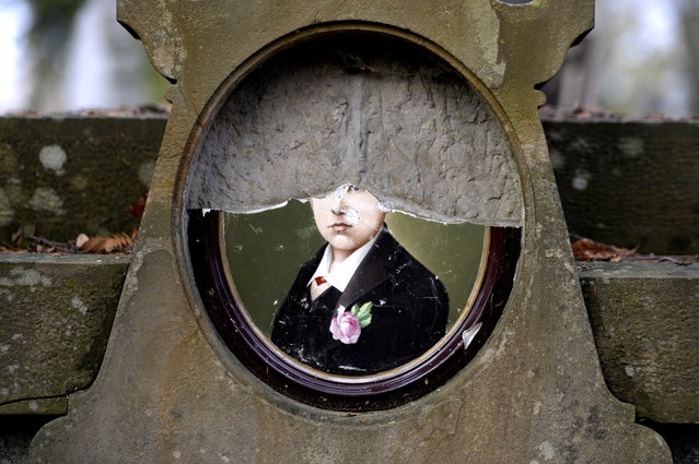 A  close-up view of half of a portrait on a Polish grave at the Lychakiv Cemetery in Lviv, Ukraine, November 1, 2014 during All Saints' Day. Created in 1787, The Lychakiv Cemetery is a famous and historic cemetery in Lviv. The original project was prepared by Karol Bauer, the head of the Lviv University botanical garden. (Photo by Darek Delmanowicz/EPA)