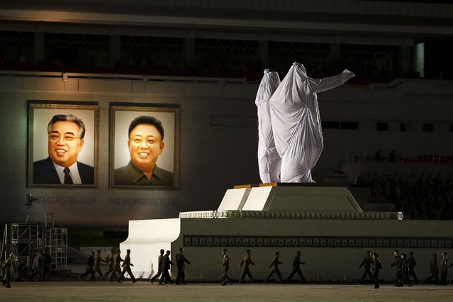 Large covered statues of North Korea's founder Kim Il-sung and former leader Kim Jong-il are wheeled past their portraits after the parade celebrating the 70th anniversary of the founding of the ruling Workers' Party of Korea, in Pyongyang October 10, 2015. (Photo by Damir Sagolj/Reuters)