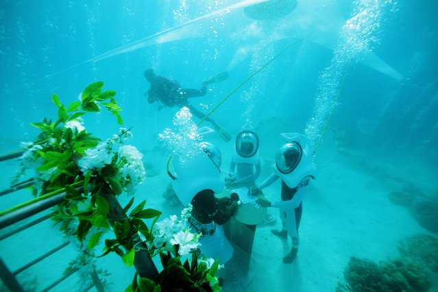 In a picture taken with an underwater camera, a couple stands in front of a Polynesian priest during their underwater wedding ceremony on October 25, 2014 in Bora-Bora, in French Polynesia. The ceremony lasts twenty minutes and costs around 2700 euros