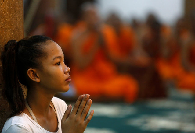 A girl prays at a pagoda during the first day of the Pchum Ben festival in Phnom Penh September 17, 2016. Cambodians visit temples during the 15-day Pchum Ben, or Festival of the Dead to offer prayers to loved ones who have passed away. (Photo by Samrang Pring/Reuters)
