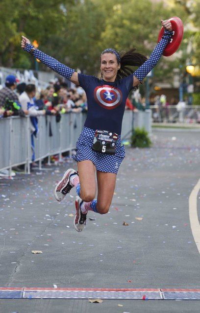 Cindy Lynch, dressed in a Captain America theme, leaps across the finish line of the Avengers Super Heroes Half Marathon in and around the Disney Parks in Anaheim, California November 16, 2014. (Photo by Eugene Garcia/Reuters)