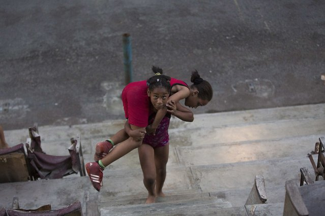 Children exercise before a wrestling practice session at an old Basque ball game gymnasium in downtown Havana, October 30, 2014. (Photo by Alexandre Meneghini/Reuters)