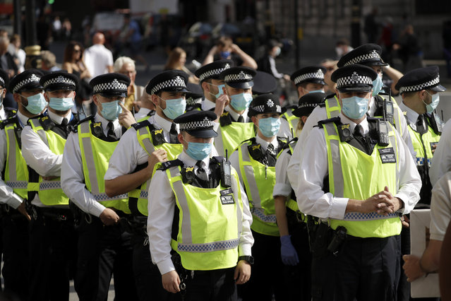 """Police officers wearing face masks stand next to a """"Resist and Act for Freedom"""" protest against a mandatory coronavirus vaccine, wearing masks, social distancing and a second lockdown, in Trafalgar Square, London, Saturday, September 19, 2020. (Photo by Matt Dunham/AP Photo)"""