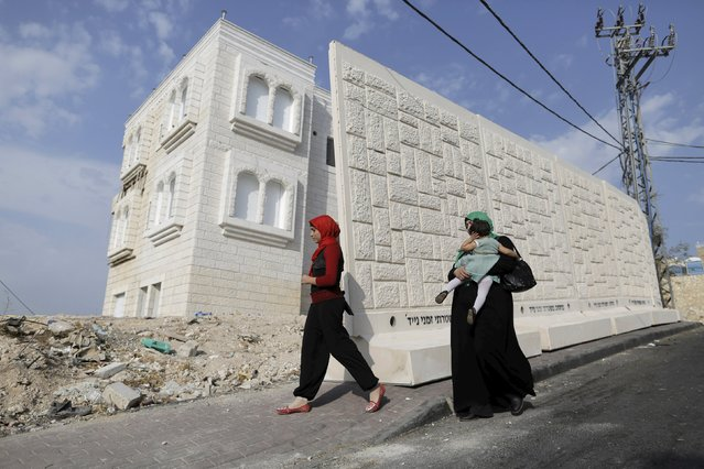 Women walk past a newly erected temporary concrete wall that measures around 10 meters in length, in the East Jerusalem neighbourhood of Jabel Mukaber October 19, 2015. (Photo by Ammar Awad/Reuters)
