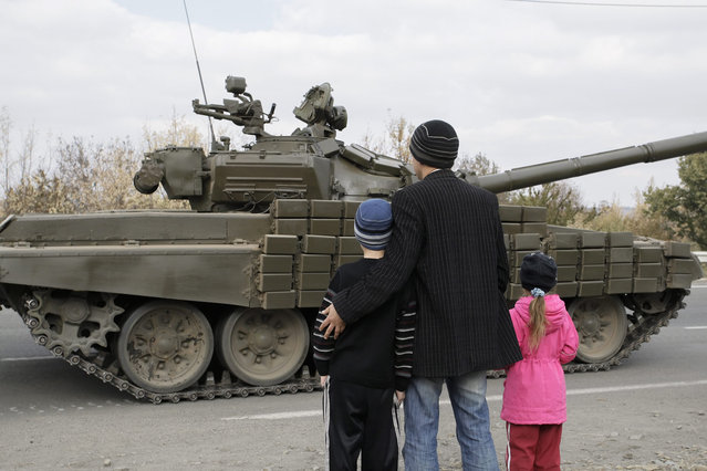 Local people look on at the Pro-Russian rebel's tank column at the Lugansk region, Ukraine, 20 October 2015. Ukraine and pro-Russian rebels continue to withdraw their guns with a caliber of less than 100 millimeters from the front line in Donetsk and Lugansk areas, in  accordance with the Minsk agreement. (Photo by Alexander Ermochenko/EPA)