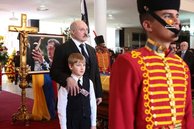 President of Belarus Alexander Lukashenko and his son Nikolai, stand next to the flag-draped coffin of late Venezuela's President Hugo Chavez during the funeral ceremony at the military academy in Caracas on March 8, 2013. (Photo by Marcelo Garcia/Miraflores Press via AP Photo)