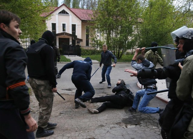 Pro-Russian protesters attack a pro-Ukranian protester during a pro-Ukrainian rally in the eastern city of Donetsk in this April 28, 2014 file photo. Around 500 people were waving Ukrainian flags and shouting anti-Russian slogans. After 30 minutes they started a protest march, but soon afterwards pro-Russian protesters turned up with baseball bats and sticks and clashes broke out. (Photo and caption by Marko Djurica/Reuters)