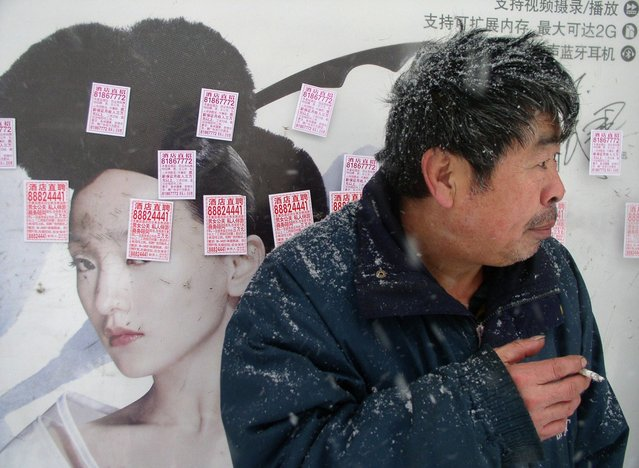 Billboard defaced with stickers advertising jobs in wintery Liaoning. (Photo by Tom Carter/The Atlantic)