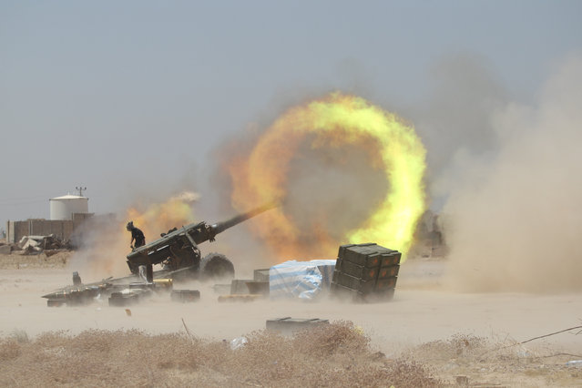 An Iraqi Shi'ite fighter fires artillery during clashes with Islamic State militants near Falluja, Iraq, May 29, 2016. (Photo by Reuters/Stringer)