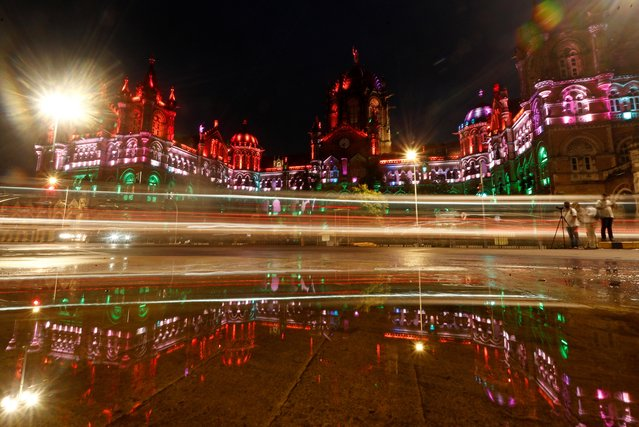 Traffic moves in front of the Chhatrapati Shivaji Maharaj Terminus (CSMT) building as it is illuminated in the colours of India's national flag during Independence Day celebrations in Mumbai, India, August 15, 2020. (Photo by Francis Mascarenhas/Reuters)
