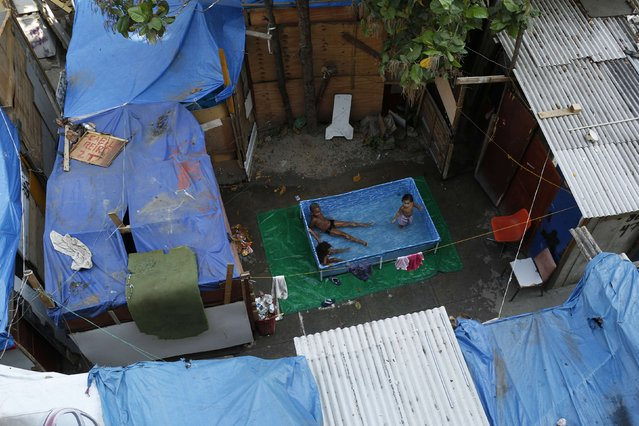 Children sit in a pool among makeshift homes, part of the Nova Tuffy slum, in an abandoned factory compound in Rio de Janeiro, in this October 17, 2014 file photo. (Photo by Pilar Olivares/Reuters)