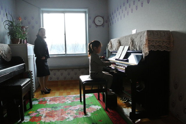 This picture taken on December 15, 2012 shows a North Korea teacher (L) during a music class at a nursery school in the North Korean border town of Siniuju, across from China's northeastern city of Dandong. (Photo by Wang Zhao/AFP Photo)