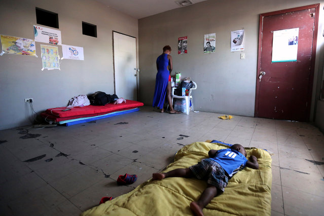 A Haitian migrant is seen as a child rests inside a shelter where they were relocated to after leaving Brazil due to Haiti's 2010 earthquake, in Mexicali, Mexico, October 5, 2016. (Photo by Edgard Garrido/Reuters)