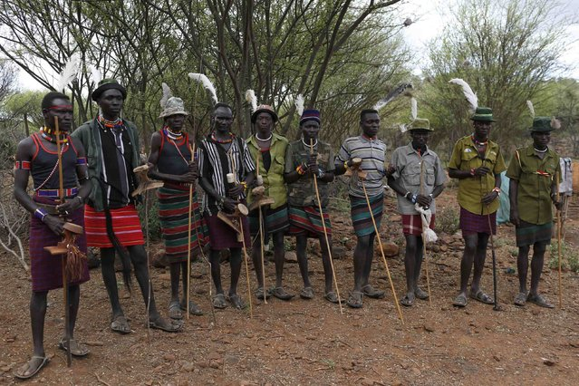 Pokot men stand near the home of a girl to be taken as wife for a member of their group, about 80 km (50 miles) from the town of Marigat in Baringo County December 7, 2014. (Photo by Siegfried Modola/Reuters)