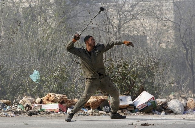 A Palestinian uses a sling to hurl stones towards Israeli troops during clashes in the West Bank village of Beit Ommar, north of Hebron November 3, 2015. Israel shut down the main radio station in Hebron on Tuesday and turned part of the city in the occupied West Bank into a closed military zone, with troops clamping down on a district that has become the focal point of violent unrest. (Photo by Mussa Qawasma/Reuters)