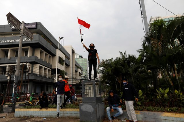 A demonstrator holds a flag during a protest against the new so-called omnibus law, in Jakarta, Indonesia, October 13, 2020. (Photo by Willy Kurniawan/Reuters)