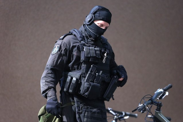 A heavily armed police officer walks near Lindt cafe, where hostages are being held,in Martin Place in central Sydney December 15, 2014. Australian police locked down the centre of the country's biggest city on Monday after an armed assailant walked into a downtown Sydney cafe, took hostages and forced them to display an Islamic flag, igniting fears of a jihadist attack. (Photo by David Gray/Reuters)