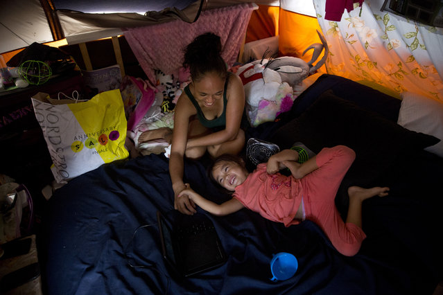 In this Wednesday, August 26, 2015 photo, Tabatha Martin, 27, plays with her 4-year-old daughter, Thalia, in their tent at a homeless encampment in the Kakaako district of Honolulu. The Martins became homeless when Tracy, the father, had a heart attack after working long hours as a kitchen manager, they said. After exhausting their savings, they couldn't afford rent for their Pearl City apartment and wound up on the street. (Photo by Jae C. Hong/AP Photo)