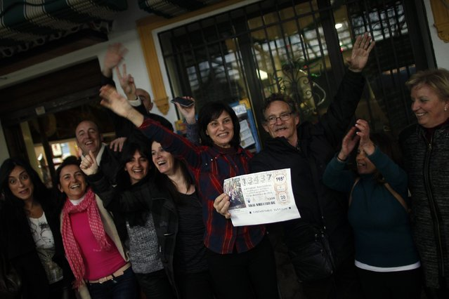 """A lottery seller (3rd R) holds a sign with the winning number of Spain's Christmas Lottery """"El Gordo"""" next to winners as they celebrate in Arriate, near Malaga, southern Spain December 22, 2014. (Photo by Jon Nazca/Reuters)"""