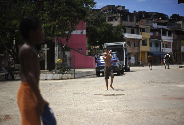 A boy plays on the street of the Nordeste de Amaralina slum complex in Salvador, Bahia State, March 28, 2013. One of Brazil's main tourist destinations and a 2014 World Cup host city, Salvador suffers from an unprecedented wave of violence with an increase of over 250% in the murder rate, according to the Brazilian Center for Latin American Studies (CEBELA). Picture taken March 28, 2013. (Photo by Lunae Parracho/Reuters)