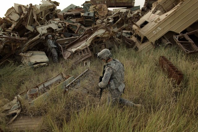 U.S. Army Lt. Christopher Chavez, 28, from Sacramento, Calif., center, and Staff Sgt. Michael Snyder, left, 35, from Glendale, Ariz., of D Co., 1st Battalion, 18th Infantry Regiment, search a Saddam Hussein-era military vehicle graveyard outside Contingency Operating Site Taji, north of Baghdad, Iraq, Sunday, August 7, 2011. (Photo by Maya Alleruzzo/AP Photo)