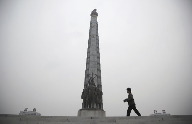 """A North Korean woman is silhouetted as she walks past the Juche Tower and residential buildings on each side with slogans on them which read """"Single Minded Unity"""" on Sunday, October 16, 2016, in Pyongyang, North Korea. (Photo by Wong Maye-E/AP Photo)"""