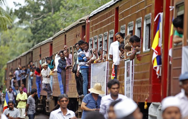 People hang onto the Sri Lankan train Samudra Devi in Pereliya December 26, 2014. The original locomotive and five of its carriages were restored in 2008 and the train headed south from Colombo on Friday at the exact same time as a decade ago, with relatives of victims and a handful of survivors on board. (Photo by Dinuka Liyanawatte/Reuters)