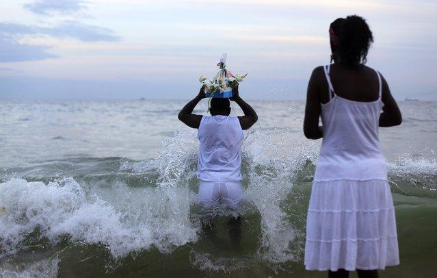 A follower of the Afro-Brazilian religion Umbanda carries offerings for Iemanja, goddess of the sea, in Copacabana Beach in Rio de Janeiro December 29, 2014. (Photo by Ricardo Moraes/Reuters)
