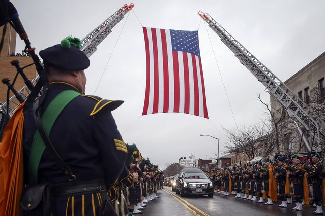 The hearse carrying NYPD officer Wenjian Liu makes its way under a U.S. flag en route to the cemetery in the Brooklyn borough of New York January 4, 2015. (Photo by Shannon Stapleton/Reuters)