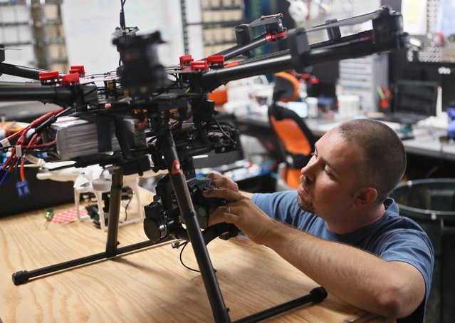 In this July 10, 2014 file photo, Greg Ledford, director of UAV Technology at Atlanta Hobby, prepares a DJI Technology S1000 professional octocopter for flight, in Cumming, Ga. The S1000 is designed for professional aerial photography and cinematography. (Photo by Bob Andres/AP Photo/Atlanta Journal-Constitution)