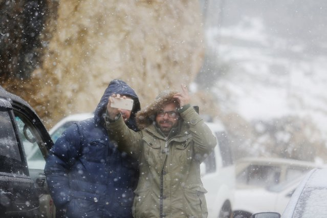 Palestinians take a photo as snow falls in the West Bank city of Ramallah on Friday, January 9, 2015. Snow fell in parts of the Middle East on Wednesday as a powerful winter storm swept through the region. Palestinian authorities in the West Bank and Gaza Strip have declared a state of emergency over the storm. (Photo by Nasser Shiyoukhi/AP Photo)