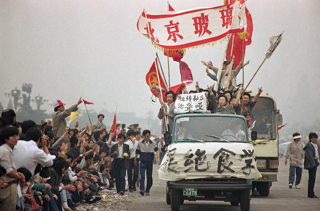 Enthusiastic demonstrators are cheered by bystanders as they arrive at Tiananmen Square to show support for the student hunger strike, on May 18, 1989. (Photo by Sadayuki Mikami/AP Photo)