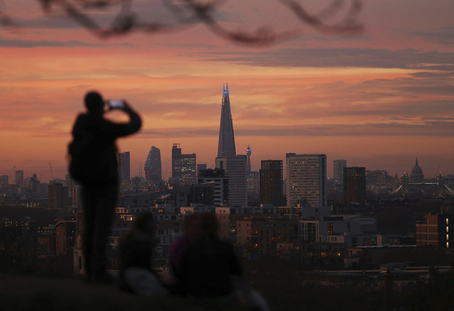 A person takes a photo of the skyline with the Shard building in the center, at sunset, from Greenwich Park in London, Tuesday, November 24, 2020. (Photo by Yui Mok/PA Wire via AP Photo)