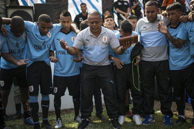 Inmates pray before playing a soccer match the in San Juan de Lurigancho prison, in Lima, Peru, Thursday, May 24, 2018. (Photoby Rodrigo Abd/AP Photo)