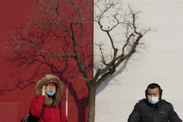 Residents wearing masks to protect from the coronavirus cross a junction in Beijing on Wednesday, January 20, 2021. (Photo by Ng Han Guan/AP Photo)