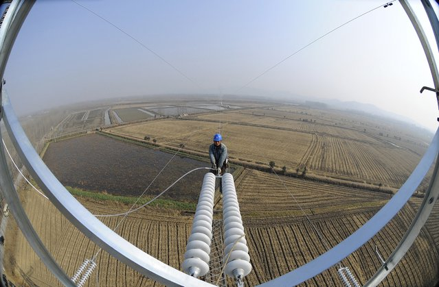 A worker installs electricity transmission components on an electricity pylon in Chuzhou, Anhui province January 12, 2015. China's annual economic growth likely slowed to 7.2 percent in the fourth quarter, the weakest since the depths of the global crisis, a Reuters poll showed, which would keep pressure on policymakers to head off a sharper slowdown this year. (Photo by Reuters/Stringer)