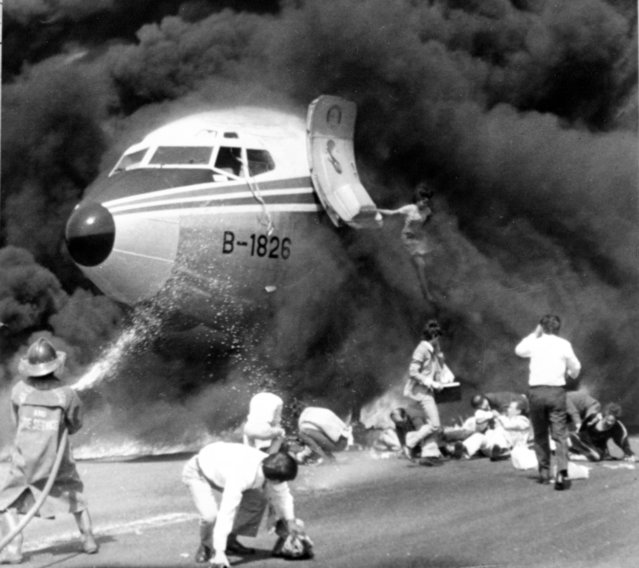 China Airlines stewardess Wang Wen Hwang leaps from the burning China Airlines plane after assisting the passengers to safety February 27, 1980. Miss Wang saved most of the lives of the passengers despite her injuries. She was the last to leave the planes. (Photo by AP Photo)