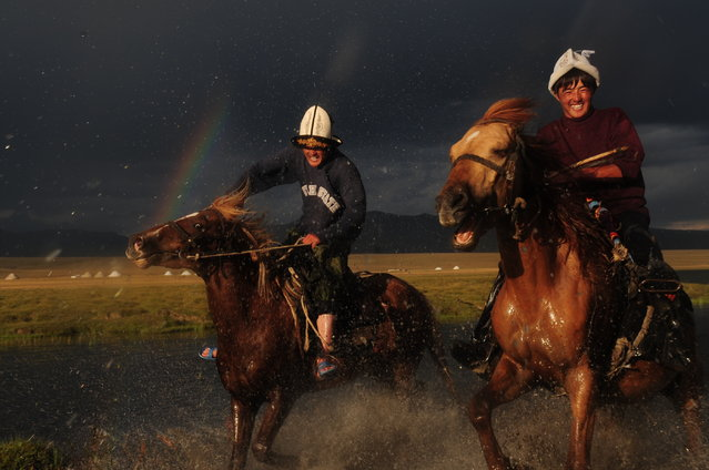 """Galloping Horses"". Galloping horses under the rainbow in song kol lake in kirghystan on a rainy day. Location: Kirghystan, Song Kol Lake, June 2011. (Photo and caption by Deniz Bensason/National Geographic Traveler Photo Contest)"