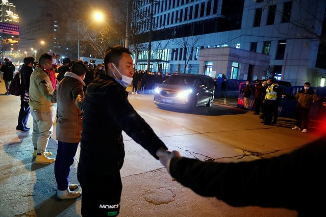 Security personnel forms a cordon as the convoy carrying the World Health Organization (WHO) team tasked with investigating the origins of the coronavirus disease (COVID-19) pandemic leaves the Wuhan Center for Disease Control and Prevention, in Wuhan, China on February 1, 2021. (Photo by Thomas Peter/Reuters)
