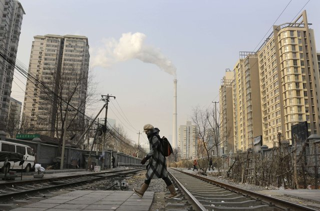 A woman walks across the railway near a heating plant on a hazy day in Beijing January 20, 2015.  Picture taken on January 20, 2015. (Photo by Jason Lee/Reuters)