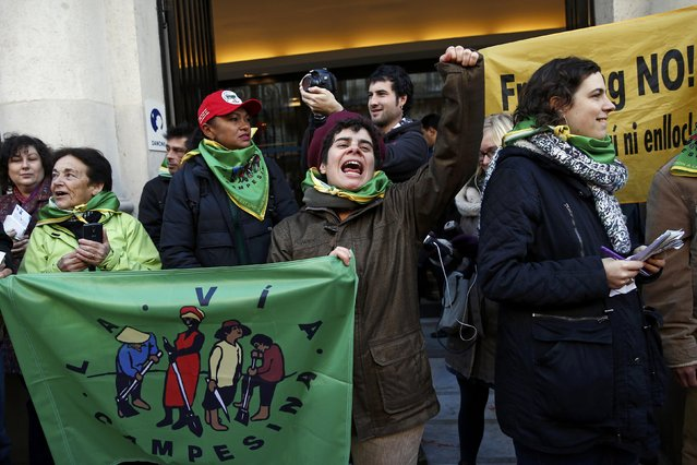 "Activists of ""Via Campesina"" gather during a protest in front of the headquarters of French food and drink company Danone, in Paris, France, December 9, 2015, as the World Climate Change Conference 2015 (COP21) continues at Le Bourget near the French capital. (Photo by Benoit Tessier/Reuters)"