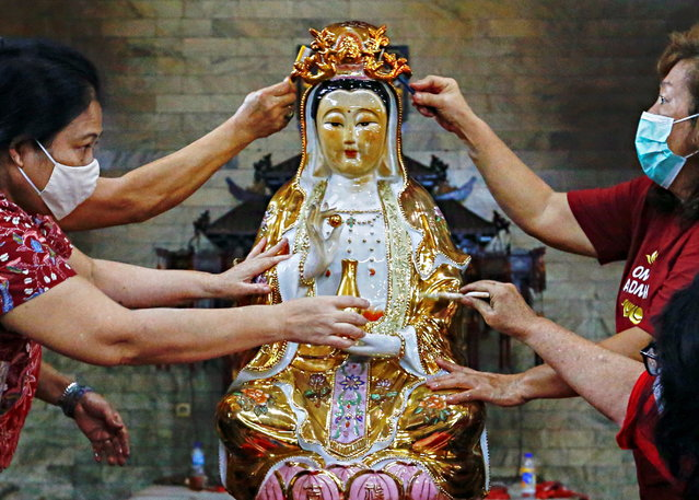 Women wearing protective face masks wash a religious statue ahead of the Chinese Lunar New Year celebration following the coronavirus disease (COVID-19) outbreak, at a temple in Jakarta, Indonesia, February 4, 2021. (Photo by Ajeng Dinar Ulfiana/Reuters)