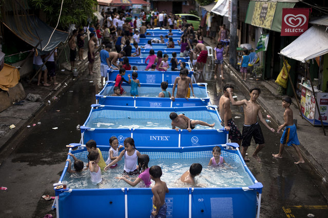 Children play in portbale pools, a project from the local government, to beat the summer heat in Manila, Philippines on April 12, 2018. (Photo by Noel Celis/AFP Photo)
