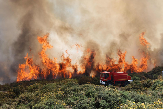 A firefighter vehicle is seen next to a fire near Saint-Paul, on the French Indian Ocean island of La Reunion, on November 8, 2020. A fire, going on for three days in Reunion Island, has so far ravaged more than 200 hectares of vegetation in the Maido massif, a reservoir of biodiversity in the west of the island. (Photo by Richard Bouhet/AFP Photo)